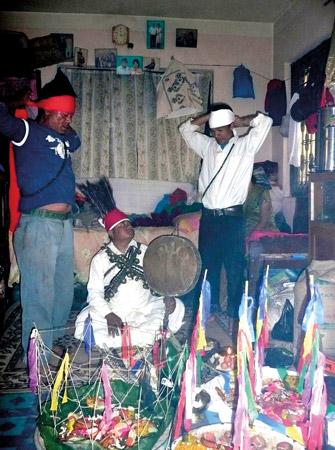 Zwei Helfer unterstützen den Schamanen bei dem großen Ritual