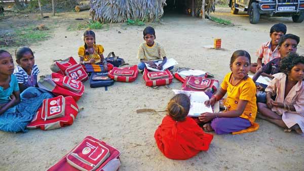 Schulkinder erhalten Nachhilfe abends im Freien.