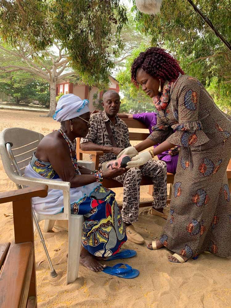 Georgette Single von Villa Karo, Mamissi DaPovi und Ananin Ghanganisou (beide Mitglieder der UCTT) mit einer Mami Wata Skulptur, die zurück gegeben wird. Übergabe der Skulptur in Villa Karo.